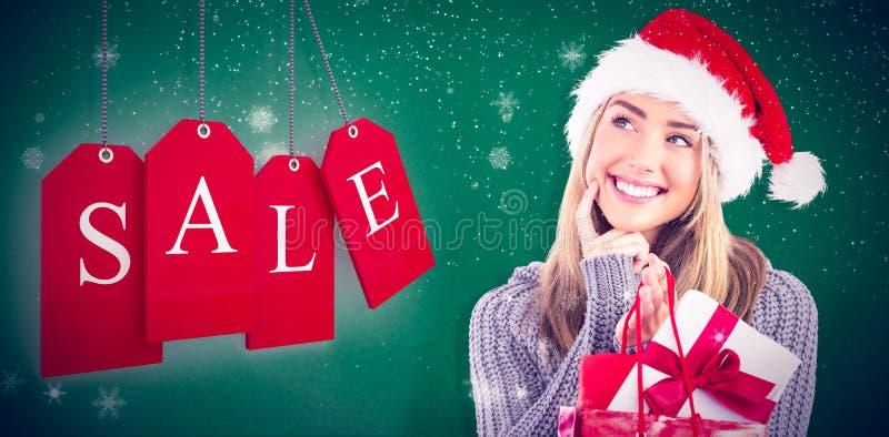 Σύνθετη εικόνα του εορταστικών ξανθών δώρου και της τσάντας Χριστουγέννων εκμετάλλευσης στοκ εικόνα
