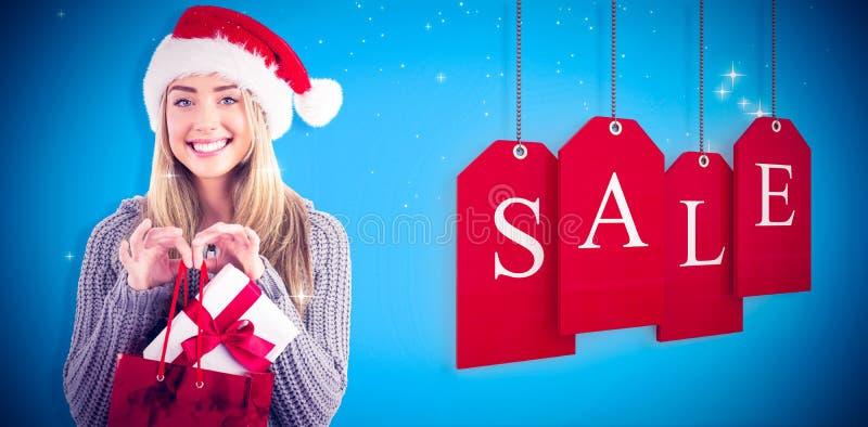 Σύνθετη εικόνα του εορταστικών ξανθών δώρου και της τσάντας Χριστουγέννων εκμετάλλευσης στοκ φωτογραφία με δικαίωμα ελεύθερης χρήσης