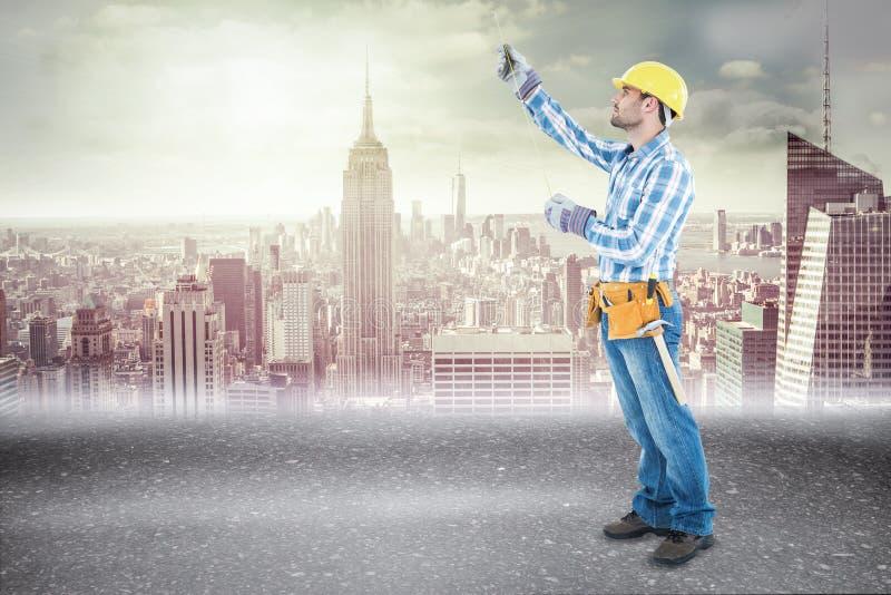 Σύνθετη εικόνα του εργάτη οικοδομών που χρησιμοποιεί την ταινία μέτρου στοκ φωτογραφία