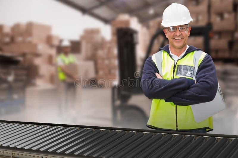 Σύνθετη εικόνα του εργαζομένου που φορά το σκληρό καπέλο στην αποθήκη εμπορευμάτων στοκ εικόνες