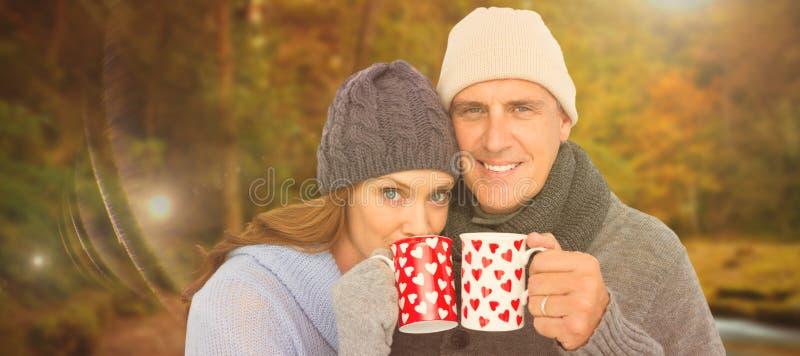 Σύνθετη εικόνα του ευτυχούς ζεύγους στις θερμές κούπες εκμετάλλευσης ιματισμού στοκ φωτογραφία με δικαίωμα ελεύθερης χρήσης
