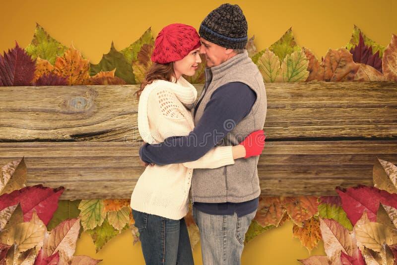 Σύνθετη εικόνα του ευτυχούς ζεύγους στο θερμό αγκάλιασμα ιματισμού στοκ εικόνες
