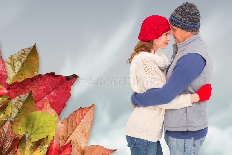 Σύνθετη εικόνα του ευτυχούς ζεύγους στο θερμό αγκάλιασμα ιματισμού στοκ εικόνα