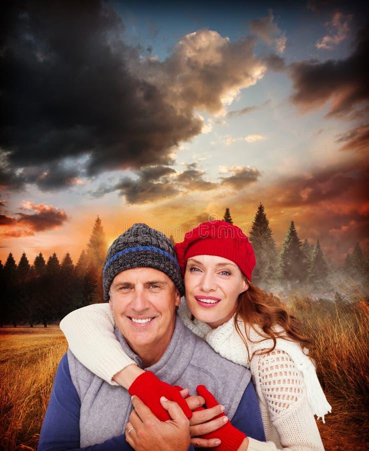 Σύνθετη εικόνα του ευτυχούς ζεύγους στο θερμό ιματισμό στοκ εικόνες