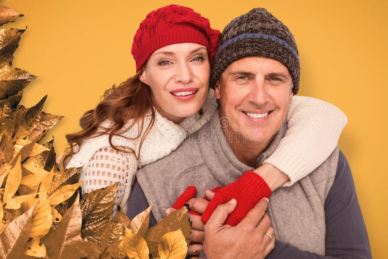 Σύνθετη εικόνα του ευτυχούς ζεύγους στο θερμό ιματισμό στοκ φωτογραφίες