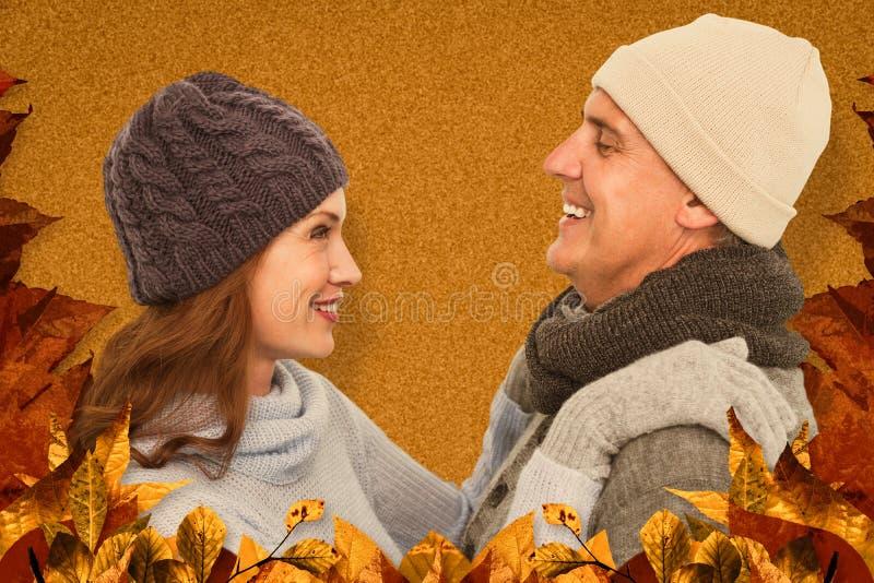 Σύνθετη εικόνα του ευτυχούς ζεύγους στο θερμό ιματισμό στοκ εικόνα
