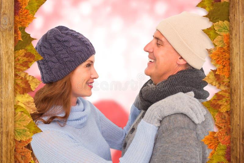 Σύνθετη εικόνα του ευτυχούς ζεύγους στο θερμό ιματισμό στοκ εικόνα με δικαίωμα ελεύθερης χρήσης