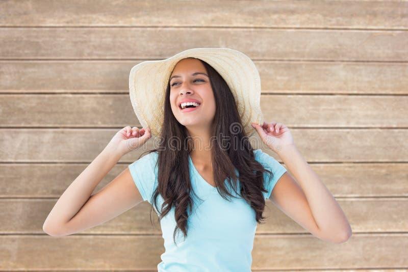 Σύνθετη εικόνα του ευτυχούς νέου brunette που φορά το ψαθάκι στοκ εικόνες