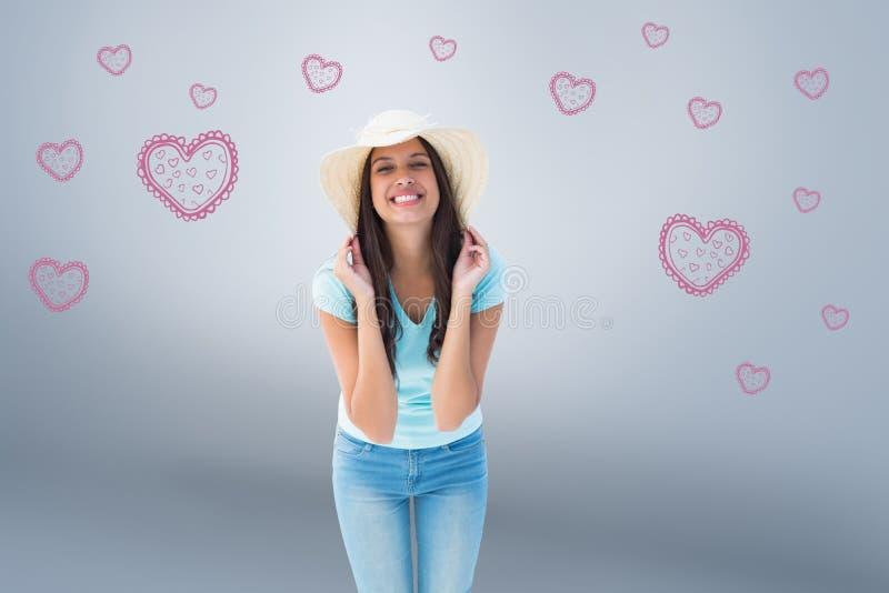 Σύνθετη εικόνα του ευτυχούς νέου brunette που φορά το ψαθάκι στοκ εικόνα