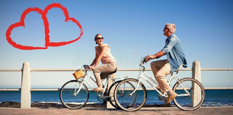 Σύνθετη εικόνα του ευτυχούς περιστασιακού ζεύγους που πηγαίνει για έναν γύρο ποδηλάτων στην αποβάθρα στοκ φωτογραφίες