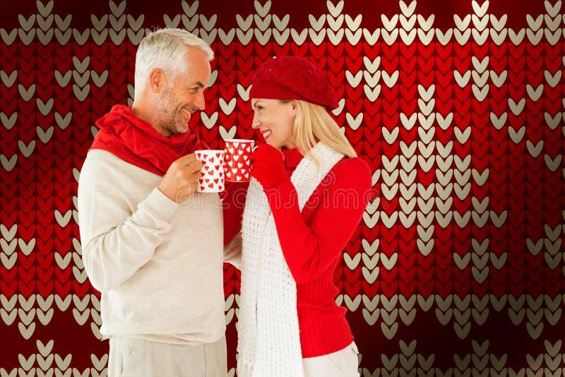 Σύνθετη εικόνα του ευτυχούς χειμερινού ζεύγους με τις κούπες στοκ εικόνες