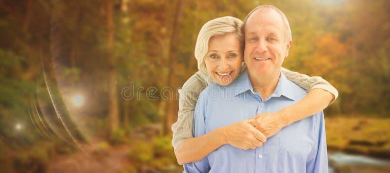 Σύνθετη εικόνα του ευτυχούς ώριμου αγκαλιάσματος ζευγών που χαμογελά στη κάμερα στοκ εικόνα