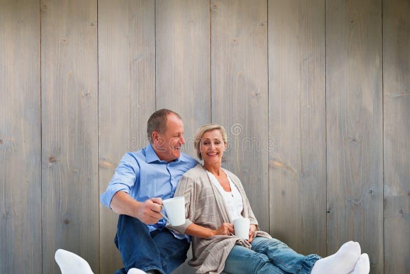 Σύνθετη εικόνα του ευτυχούς ώριμου ζεύγους που έχει τον καφέ στοκ εικόνες