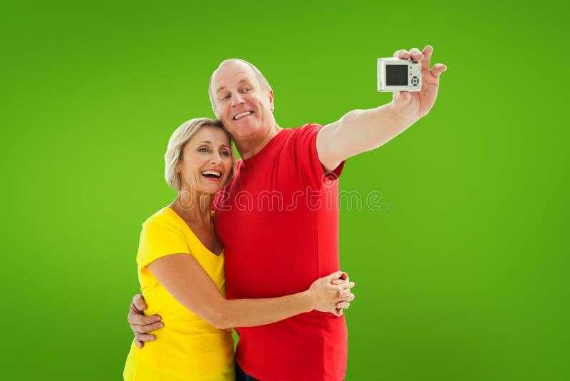 Σύνθετη εικόνα του ευτυχούς ώριμου ζεύγους που παίρνει ένα selfie από κοινού στοκ φωτογραφία