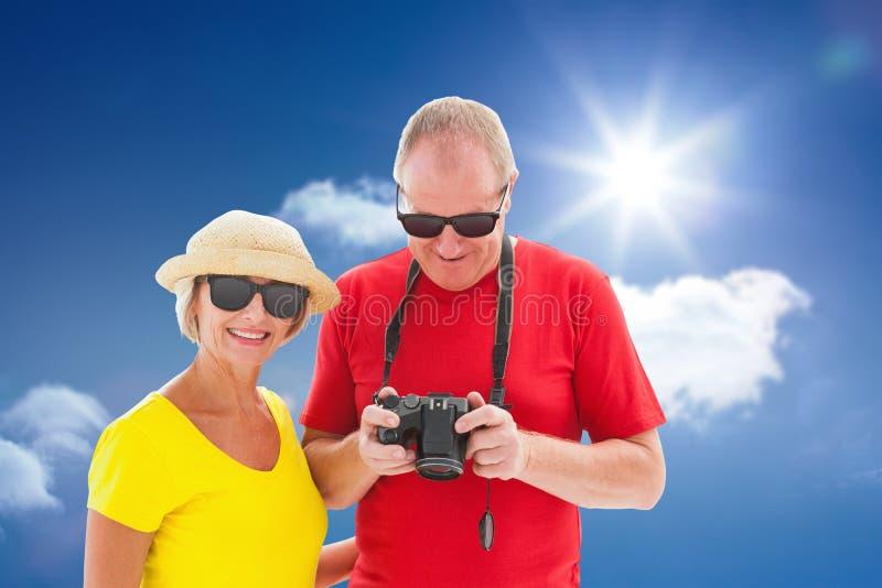 Σύνθετη εικόνα του ευτυχούς ώριμου ζεύγους που φορά τα γυαλιά ηλίου στοκ φωτογραφία με δικαίωμα ελεύθερης χρήσης