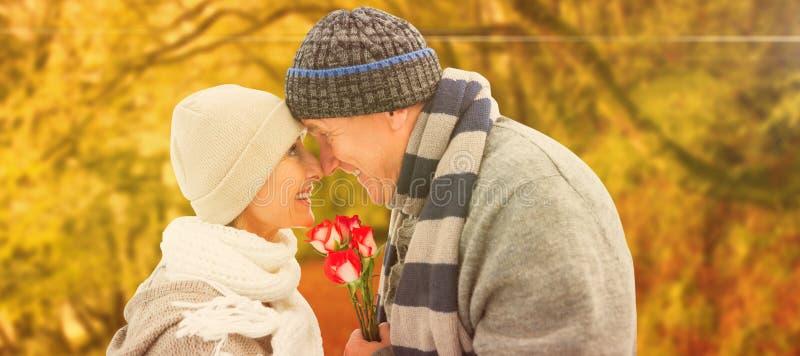 Σύνθετη εικόνα του ευτυχούς ώριμου ζεύγους στα χειμερινά ενδύματα με τα τριαντάφυλλα στοκ εικόνα με δικαίωμα ελεύθερης χρήσης