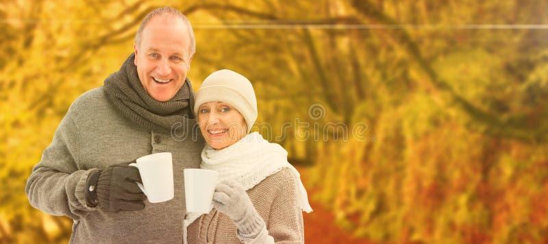 Σύνθετη εικόνα του ευτυχούς ώριμου ζεύγους στα χειμερινά ενδύματα που κρατά τις κούπες στοκ εικόνες