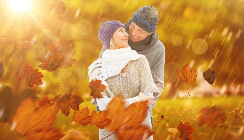 Σύνθετη εικόνα του ευτυχούς ώριμου ζεύγους στο αγκάλιασμα χειμερινών ενδυμάτων στοκ φωτογραφία