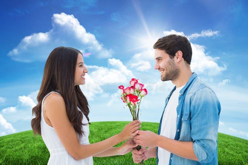 Σύνθετη εικόνα του ευτυχούς hipster που δίνει τα τριαντάφυλλα φίλων του στοκ φωτογραφία με δικαίωμα ελεύθερης χρήσης