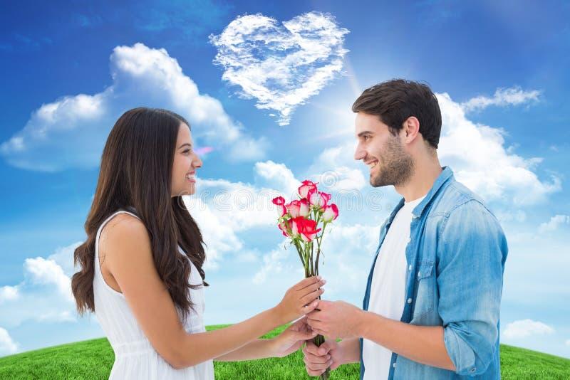 Σύνθετη εικόνα του ευτυχούς hipster που δίνει τα τριαντάφυλλα φίλων του στοκ εικόνα με δικαίωμα ελεύθερης χρήσης