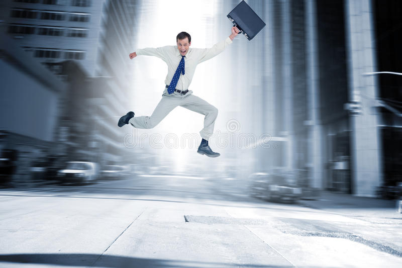 Σύνθετη εικόνα του εύθυμου πηδώντας επιχειρηματία με τη βαλίτσα του στοκ εικόνες με δικαίωμα ελεύθερης χρήσης