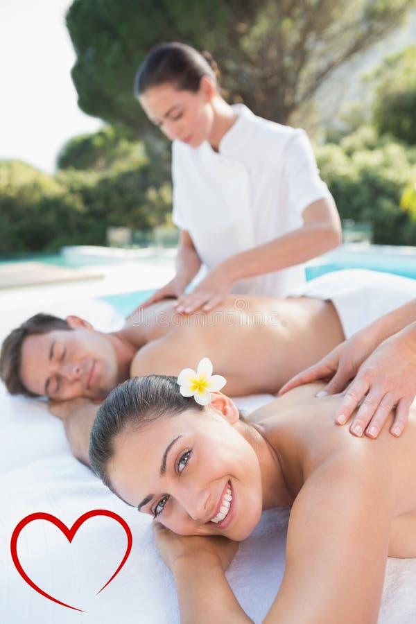 Σύνθετη εικόνα του ελκυστικού ζεύγους που απολαμβάνει το poolside μασάζ ζευγών ελεύθερη απεικόνιση δικαιώματος