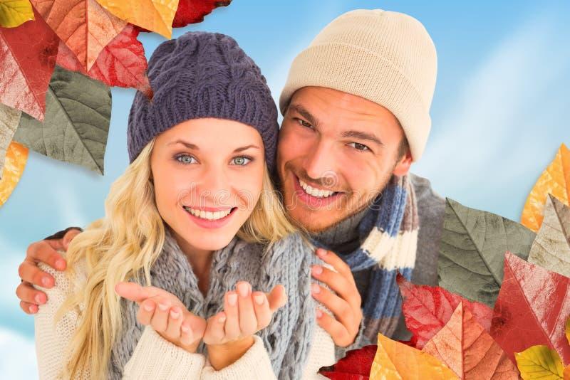 Σύνθετη εικόνα του ελκυστικού ζεύγους στη χειμερινή μόδα που χαμογελά στη κάμερα στοκ εικόνες