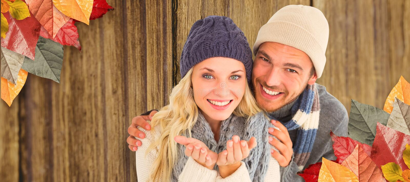 Σύνθετη εικόνα του ελκυστικού ζεύγους στη χειμερινή μόδα που χαμογελά στη κάμερα στοκ εικόνα με δικαίωμα ελεύθερης χρήσης