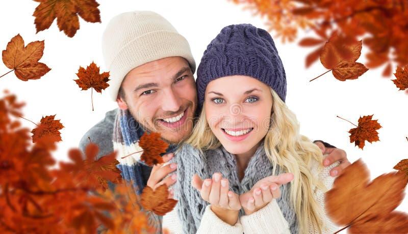 Σύνθετη εικόνα του ελκυστικού ζεύγους στη χειμερινή μόδα που χαμογελά στη κάμερα στοκ φωτογραφία