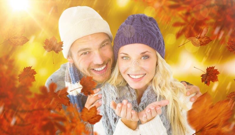 Σύνθετη εικόνα του ελκυστικού ζεύγους στη χειμερινή μόδα που χαμογελά στη κάμερα στοκ εικόνες με δικαίωμα ελεύθερης χρήσης