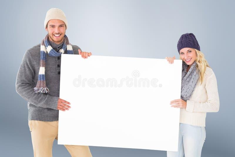 Σύνθετη εικόνα του ελκυστικού ζεύγους στη χειμερινή μόδα που παρουσιάζει αφίσα στοκ εικόνα