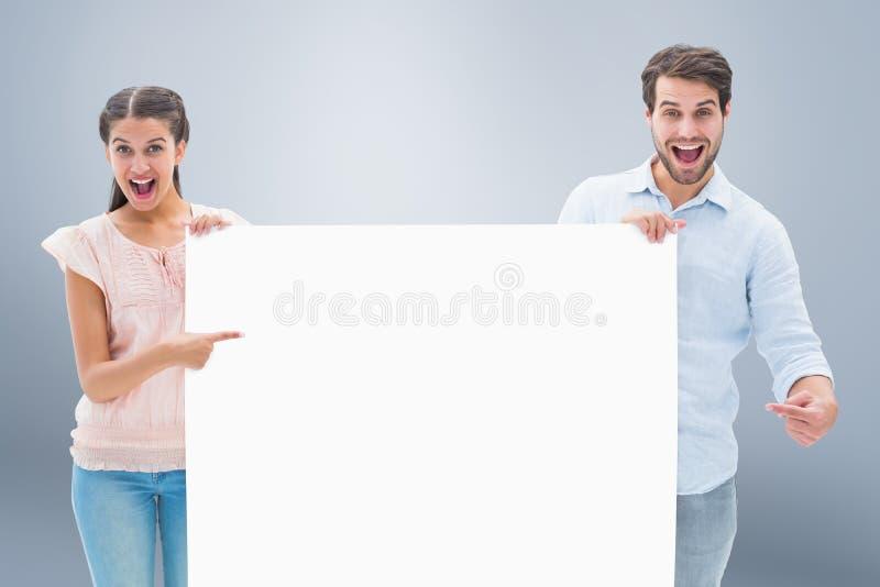 Σύνθετη εικόνα του ελκυστικού νέου ζεύγους που χαμογελά στην αφίσα εκμετάλλευσης καμερών στοκ εικόνα με δικαίωμα ελεύθερης χρήσης