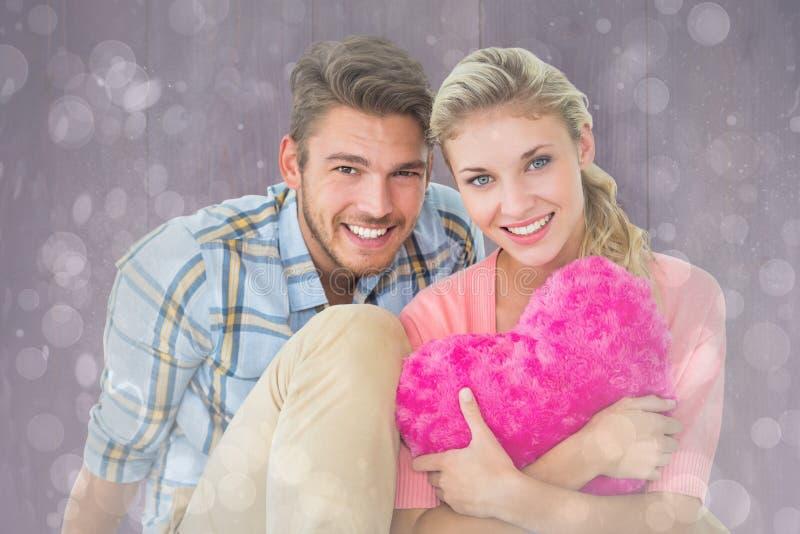 Σύνθετη εικόνα του ελκυστικού νέου μαξιλαριού καρδιών εκμετάλλευσης συνεδρίασης ζευγών στοκ φωτογραφία με δικαίωμα ελεύθερης χρήσης