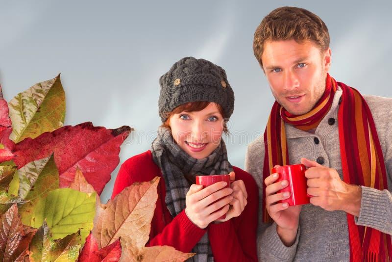 Σύνθετη εικόνα του ζεύγους και οι δύο που έχουν τα θερμά ποτά στοκ φωτογραφίες