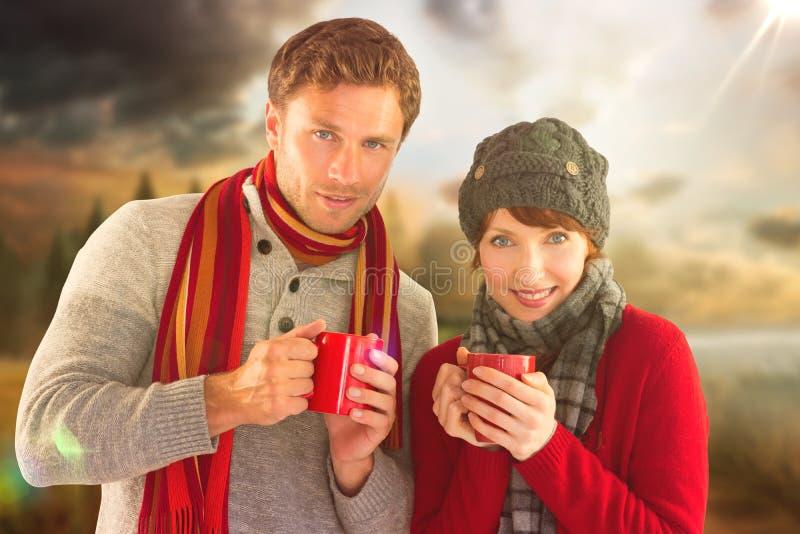 Σύνθετη εικόνα του ζεύγους και οι δύο που έχουν τα θερμά ποτά στοκ εικόνες με δικαίωμα ελεύθερης χρήσης