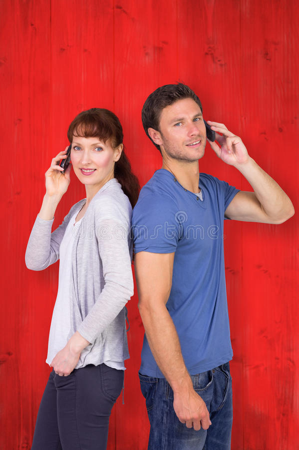 Σύνθετη εικόνα του ζεύγους και οι δύο που κάνουν τα τηλεφωνήματα στοκ εικόνες