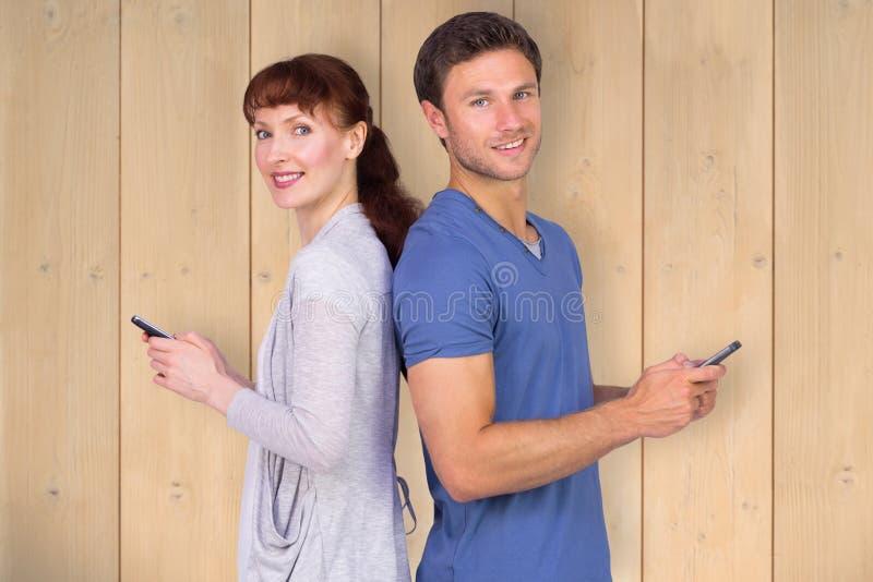 Σύνθετη εικόνα του ζεύγους και οι δύο που στέλνουν τα μηνύματα κειμένου στοκ φωτογραφίες