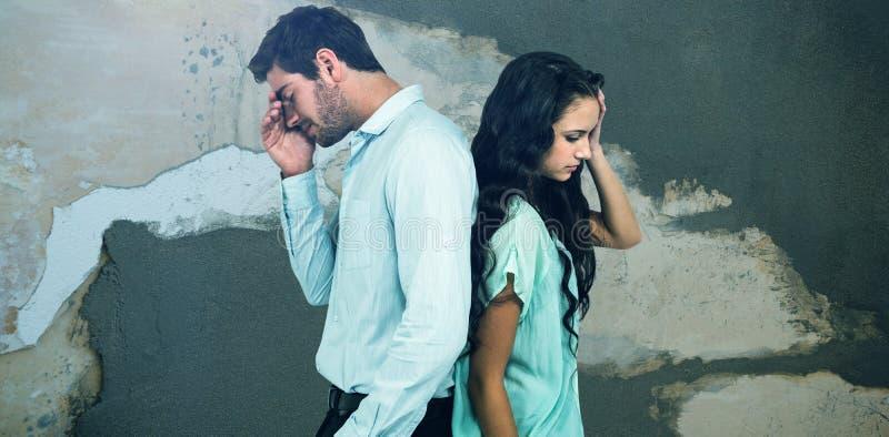 Σύνθετη εικόνα του ζεύγους με το κεφάλι στα χέρια που στέκονται πλάτη με πλάτη στοκ εικόνες με δικαίωμα ελεύθερης χρήσης