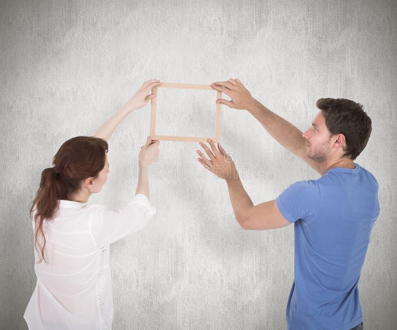 Σύνθετη εικόνα του ζεύγους που αποφασίζει να κρεμάσει την εικόνα στοκ εικόνες