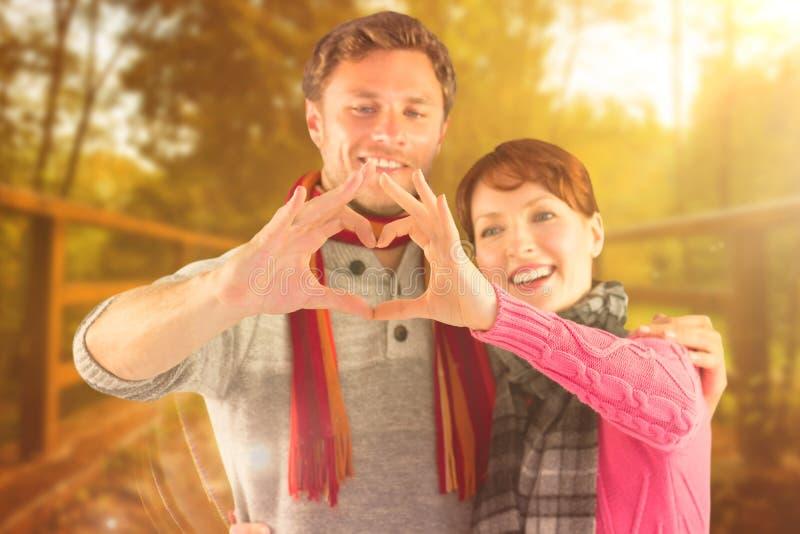 Σύνθετη εικόνα του ζεύγους που κάνει μια μορφή καρδιών στοκ φωτογραφία
