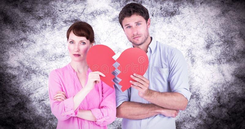Σύνθετη εικόνα του ζεύγους που κρατά μια σπασμένη καρδιά ελεύθερη απεικόνιση δικαιώματος