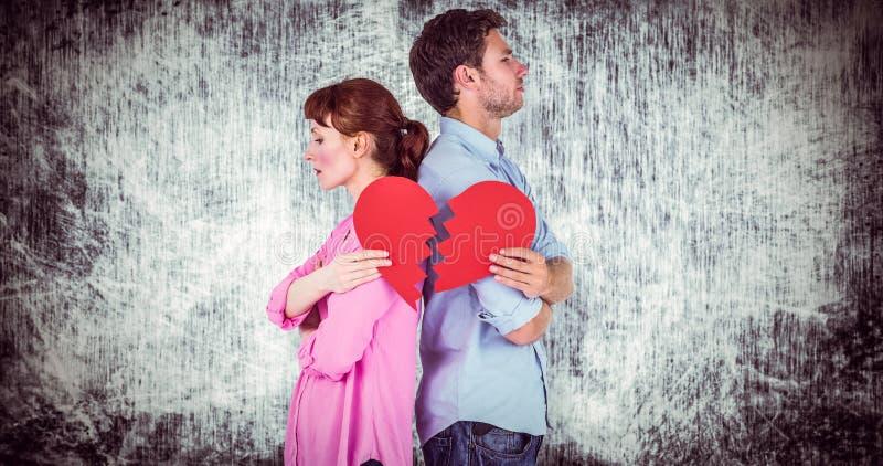 Σύνθετη εικόνα του ζεύγους που κρατά μια σπασμένη καρδιά απεικόνιση αποθεμάτων