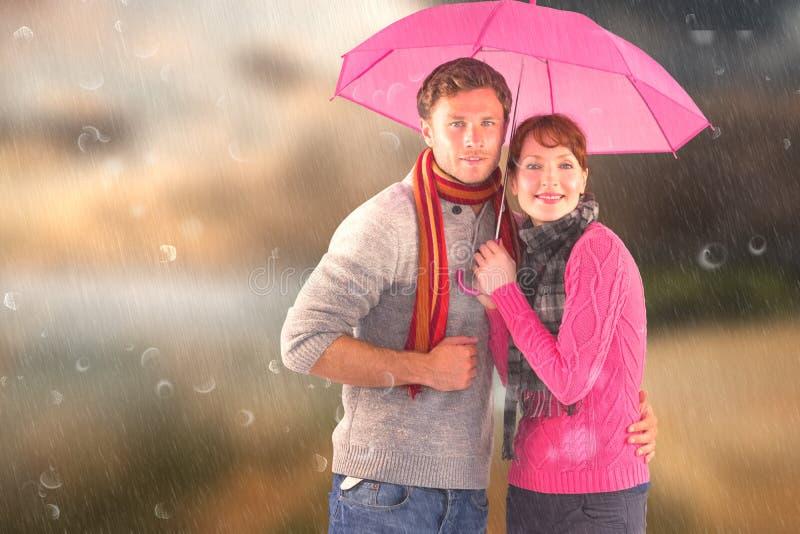 Σύνθετη εικόνα του ζεύγους που στέκεται κάτω από μια ομπρέλα στοκ εικόνα