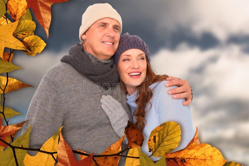 Σύνθετη εικόνα του ζεύγους στο θερμό αγκάλιασμα ιματισμού στοκ εικόνα