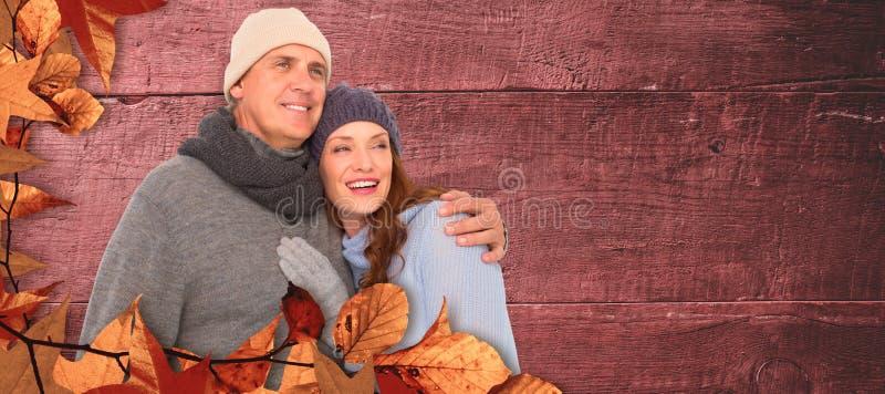 Σύνθετη εικόνα του ζεύγους στο θερμό αγκάλιασμα ιματισμού στοκ φωτογραφία
