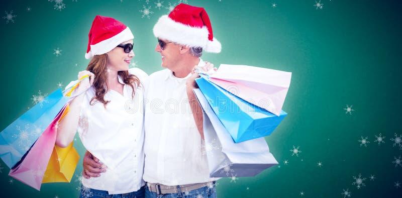 Σύνθετη εικόνα του ζεύγους Χριστουγέννων με τις τσάντες αγορών στοκ εικόνες