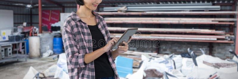 Σύνθετη εικόνα του θηλυκού αρχιτέκτονα που χρησιμοποιεί την ψηφιακή ταμπλέτα στο άσπρο κλίμα στοκ εικόνες