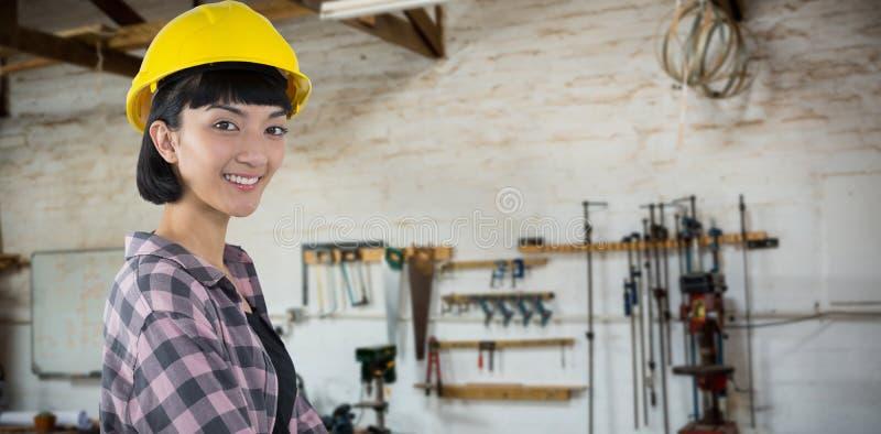 Σύνθετη εικόνα του θηλυκού αρχιτέκτονα στο σκληρό καπέλο που στέκεται στο άσπρο κλίμα στοκ εικόνα με δικαίωμα ελεύθερης χρήσης