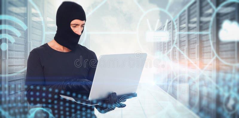 Σύνθετη εικόνα του διαρρήκτη με balaclava που χαράσσει ένα lap-top στοκ φωτογραφία με δικαίωμα ελεύθερης χρήσης