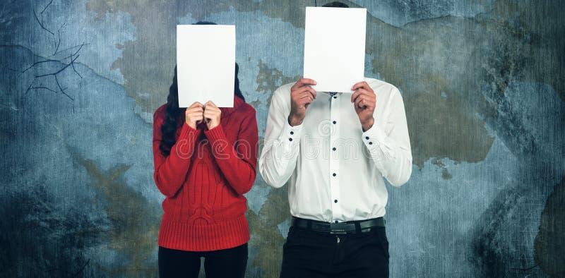 Σύνθετη εικόνα του κρύβοντας προσώπου ζευγών με τα έγγραφα στοκ φωτογραφίες με δικαίωμα ελεύθερης χρήσης